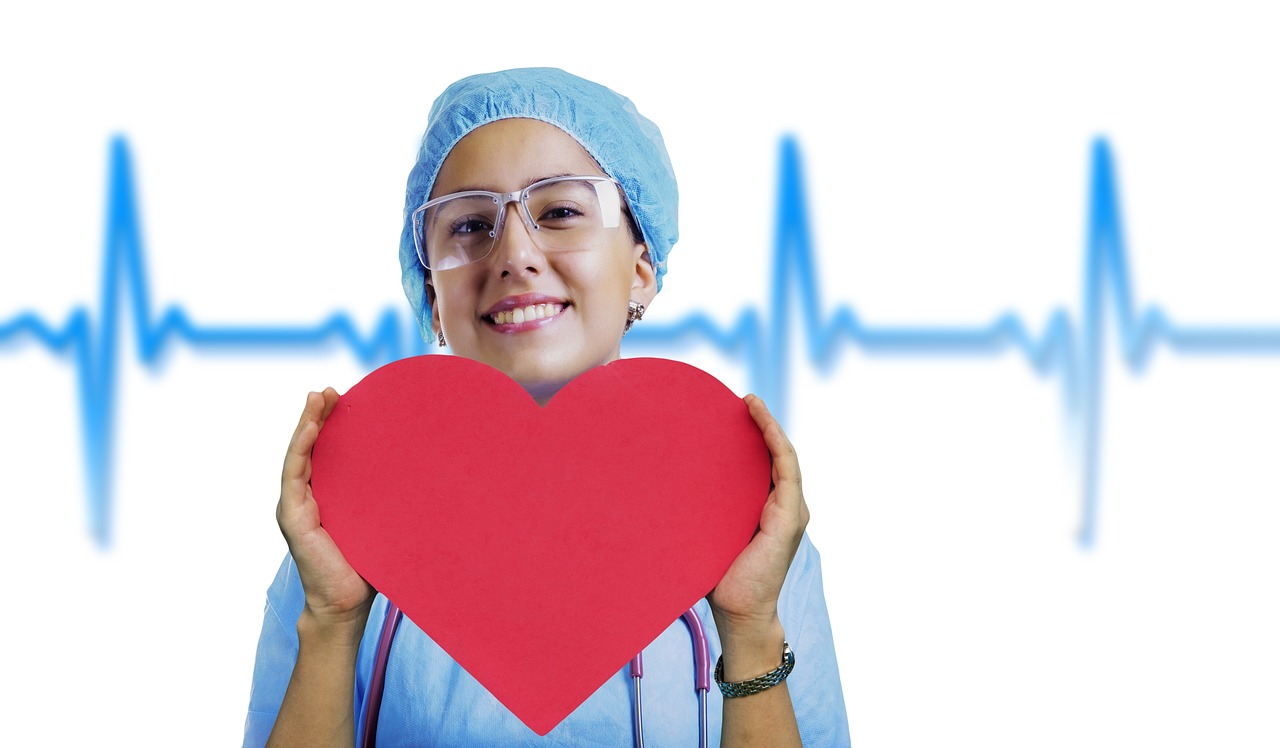 A lady wearing a medical gown goggles and at holds a heart was smiling at the camera