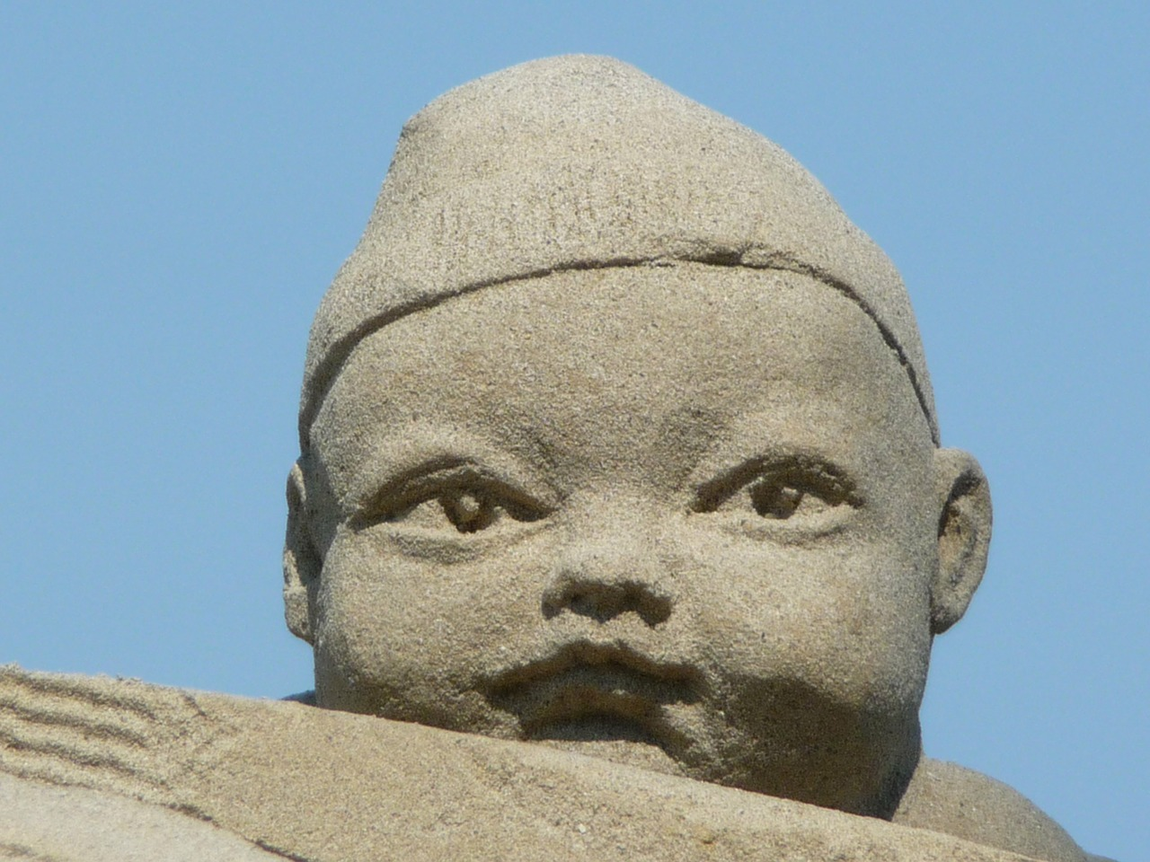 sand sculpture baby face free photo