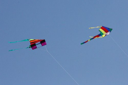 Two Colorful Kites Flying Overhead