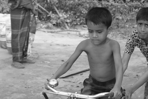 a boy try to learn cycle on the road capture this photo by other side