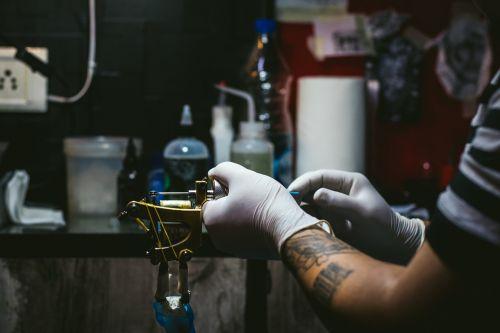 artist,tattoo,creative,tattooist,tattooing,machine,fashion,salon,skin,studio,culture,professional,lifestyle,master,body,hand,drawing,design,sterile,man,black,gloves,process,pain,ink,female,create,caucasian,concentration,needle,woman,tool,technician,style,arm