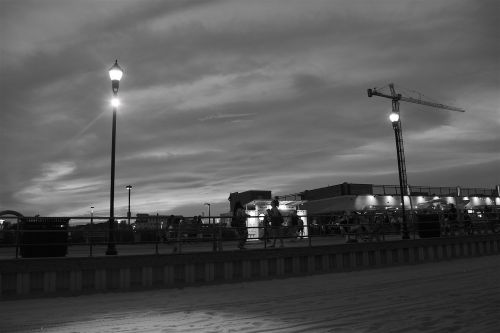 beach,evening,boardwalk,lights,shadows,summer,sunset,black and white,landscape,sand,shops,street lights