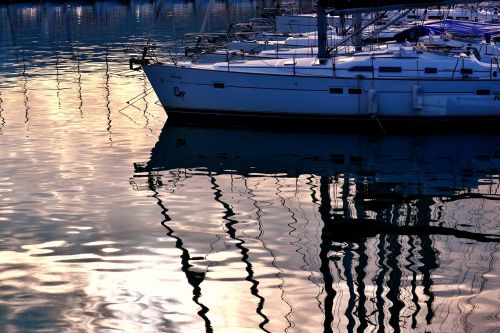 boats reflections by dawn sunset sea