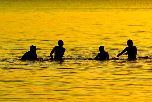 boys playing in lake  lake  dusk
