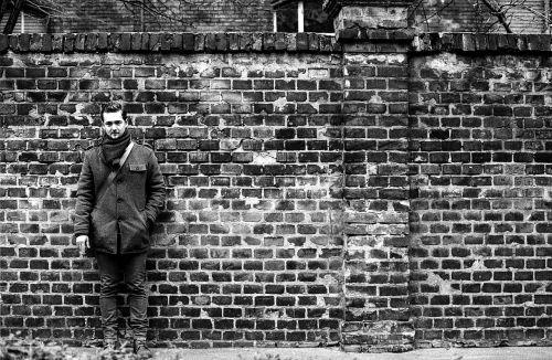 brick wall young man smoking