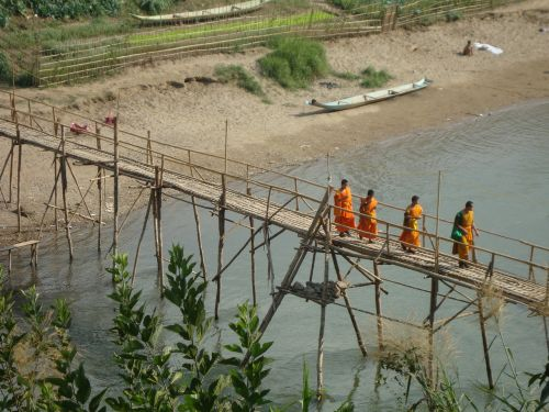 buddhist monks crossing bridge laos