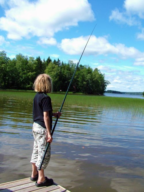 child,fish,hook and line,pier,water,reed,tree,sky,cloud