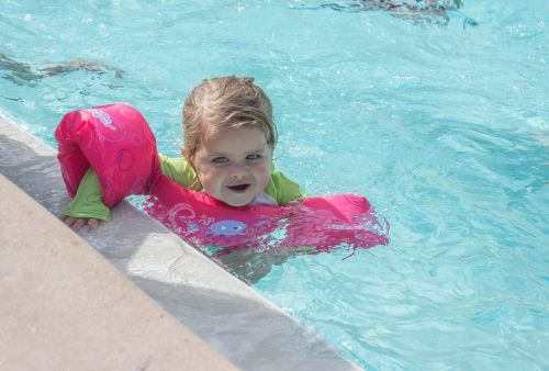 child swimming arm floats