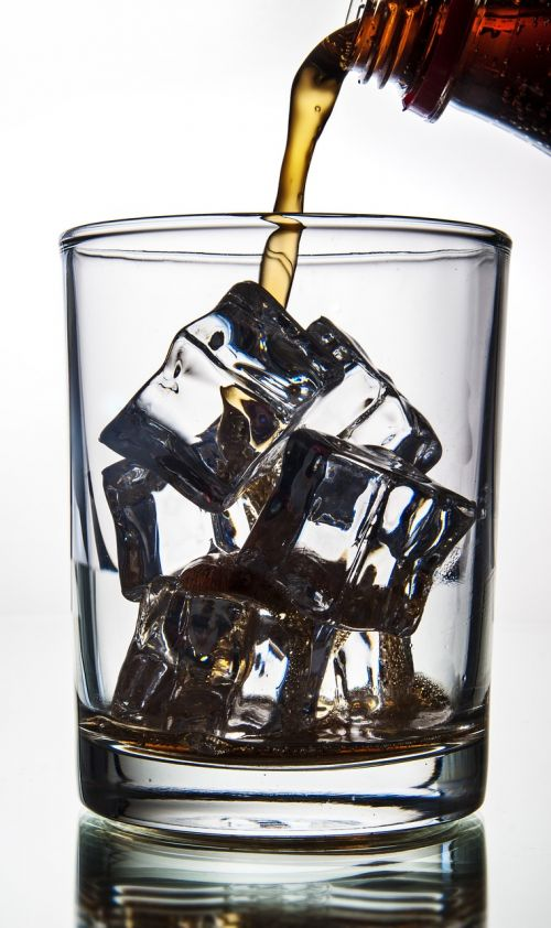cola pouring in a glass with ice ice glass