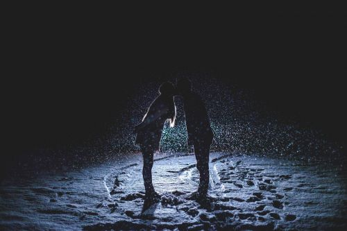 couple kissing snowy night snowing