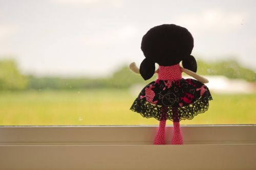 doll looking out pink