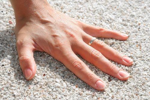 fingers hand pebbles
