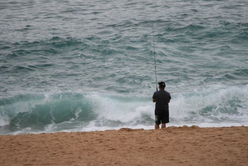 Fisherman With Waves Breaking