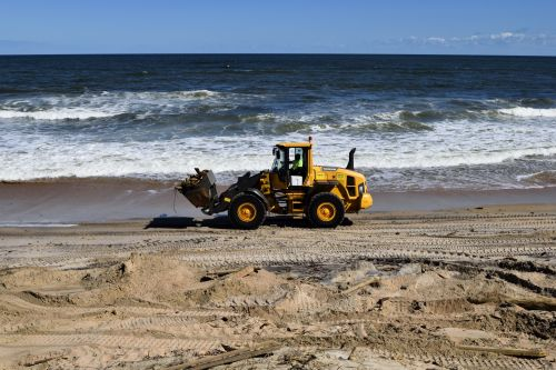 Fork Lift Cleaning Up Beach Debris