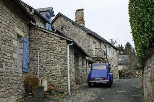 french car blue car stone alley