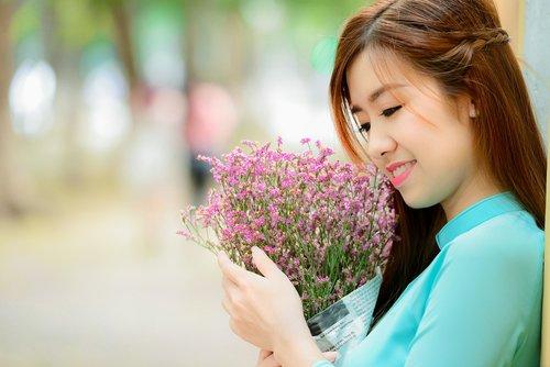 girl  long coat  smell the flowers