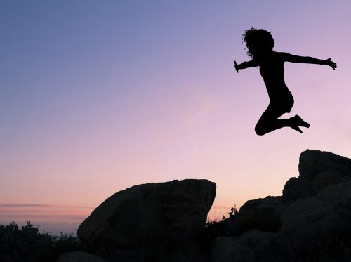 girl leaping rock