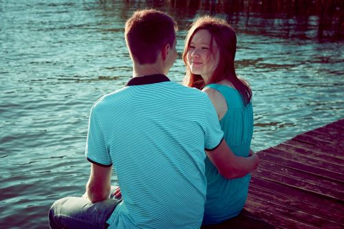 girl and guy on the shore of the pond by the water