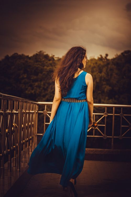 girl in a long dress from the back blue hands