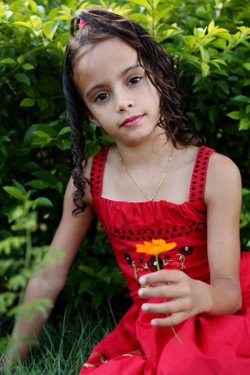 girl looking holding flower girl in the garden