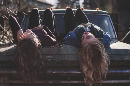 girls lying classic car