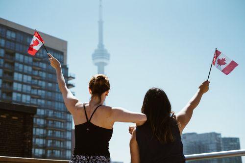 mergaitės,moterys,žmonės,Kanados,vėliavos,vakarėlis,šventė,ant stogo,terasa,toronto,cn bokštas,saulės šviesa