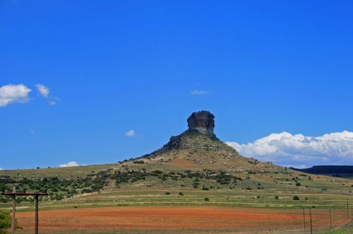 Hill With Butte Under Blue Sky