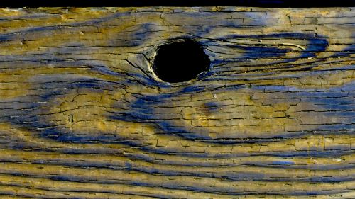 Knothole In Blue And Yellow Wood