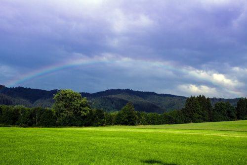 meadow clouds rainbow