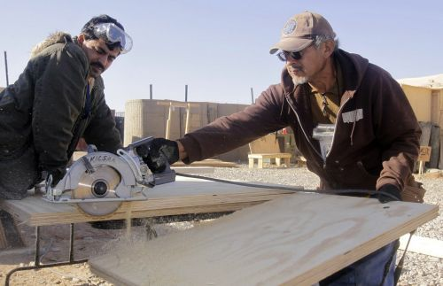 men working construction sawing