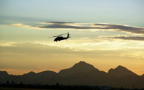 military helicopter flying dusk