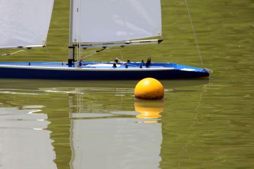 Model Yacht Behind Yellow Buoy
