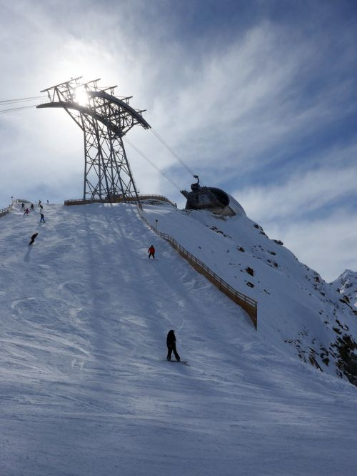 mountain,top,peak,ski,snowboard,people,sport,sun,mist,station,ski lift,lift,sky,bright,blue,snow,white,cold,wind,fun,silhouette,summit,outdoor,person,high,speed,achievement,shadow,slope,up