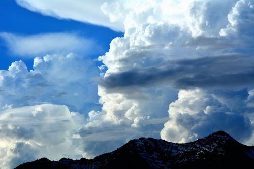 mountain peaks sky clouds