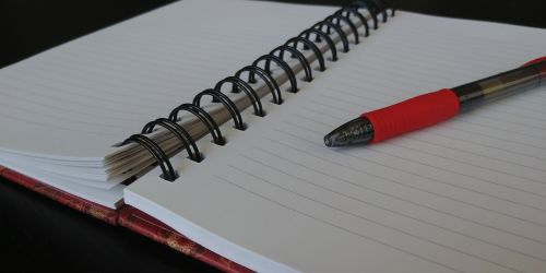 Open Notebook With Red Pen