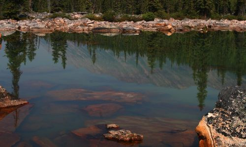 pink granite,granite,rock slide,reflection,water,still water,rocks,canadian rockies,pine trees,water reflection,rocks in water,pink,free photos,free images,royalty free