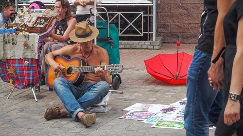 playing guitar  man  sitting on the pavement