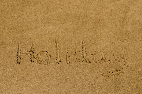"""""""Holiday"""" Written In The Sand"""