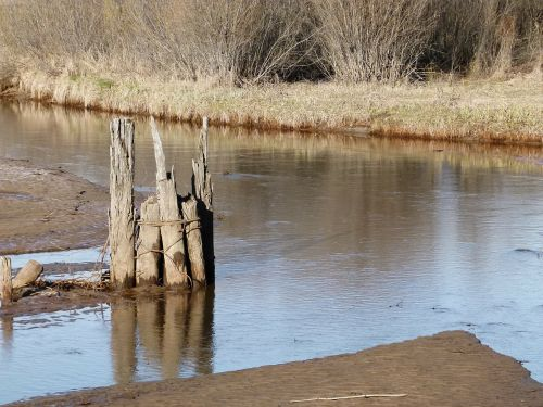 river water wooden poles
