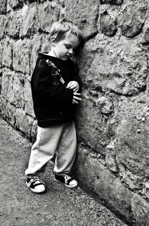 Sad Child At A Stone Wall