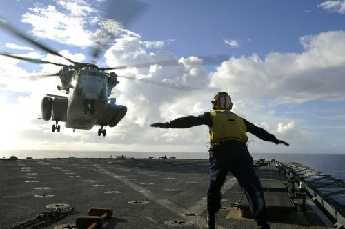 sailor directing helicopter landing ship