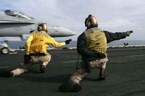 sailors signal to launch jet aircraft carrier