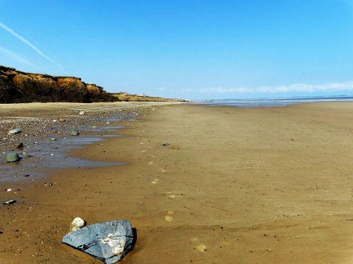 smėlis ir dangus,papludimys,Anglija,Jorkšyro pakrantė,paplūdimio smelis,smėlis,dangus,jūra,mėlynas,vanduo,vandenynas,kelionė,gamta,vasara,kranto,turizmas,kraštovaizdis,akmenukai,Rokas,pakrančių erozija,vaizdingas