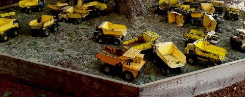 Sandbox Of Yellow Toy Trucks
