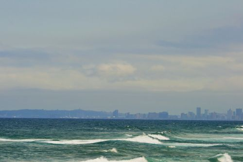 Sea With City Skyline And Bluff