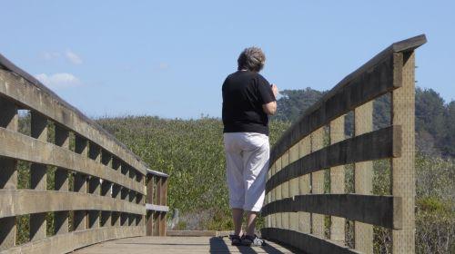 Senior Woman Walking Across Bridge