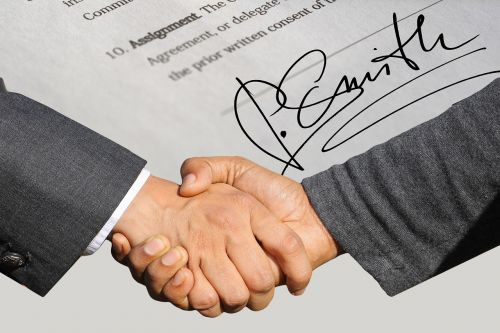signature contract shaking hands
