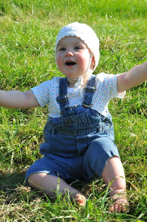 small child arms raised meadow