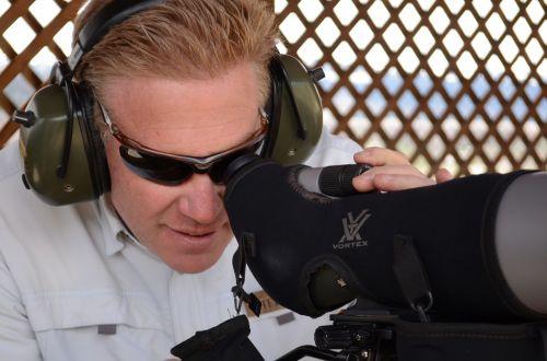 spotting scope man looking through spotting scope long range rifle spotter