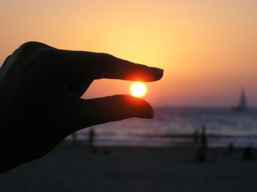 sun in the hand fingers sunset